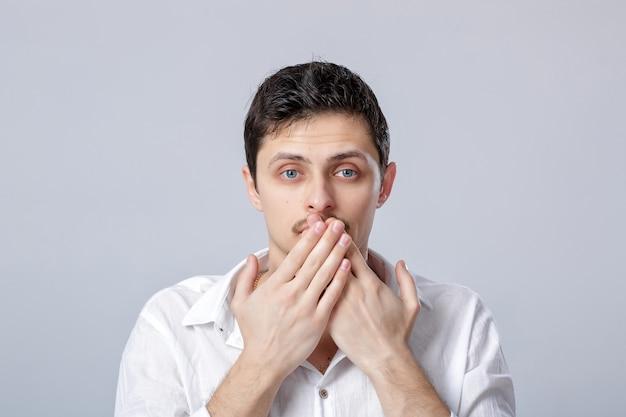 Portret van een jonge brunet man in wit overhemd bedekt zijn mond met zijn handen op een grijze achtergrond. man kent het geheim maar wil het niet vertellen