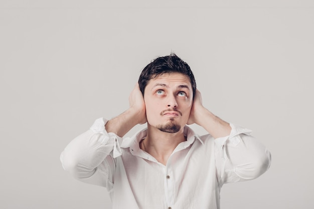 Portret van een jonge brunet man in wit overhemd bedekt zijn oren met zijn handen tegen een grijze achtergrond. ik wil niets horen. zacht licht
