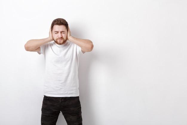 Portret van een jonge brunet man in wit overhemd bedekt zijn oren met zijn handen tegen een grijze achtergrond. ik wil niets horen