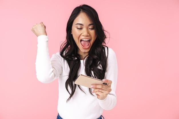 Portret van een jonge brunette aziatische vrouw met lang haar die een mobiele telefoon vasthoudt en videogames speelt die over een roze muur zijn geïsoleerd