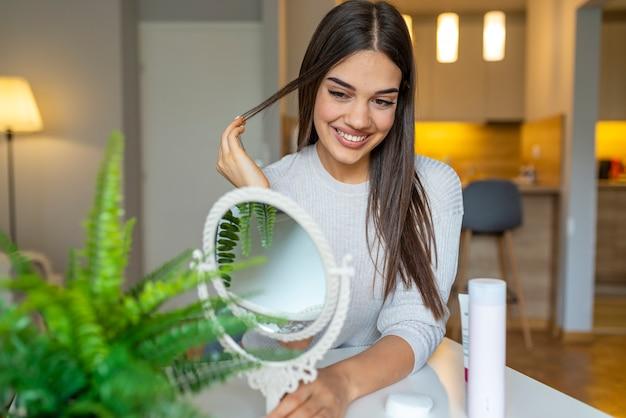 Portret van een jonge brunette cosmetica schoonheid. gelukkige jonge vrouw die op spiegel kijkt