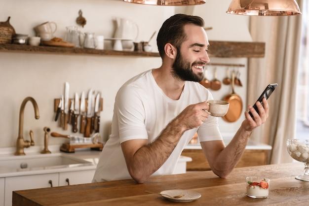 Portret van een jonge brunette man die koffie drinkt en smartphone gebruikt terwijl hij thuis ontbijt in een stijlvolle keuken