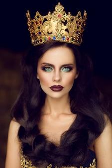 Portret van een jonge brunette vrouw die een kroon draagt