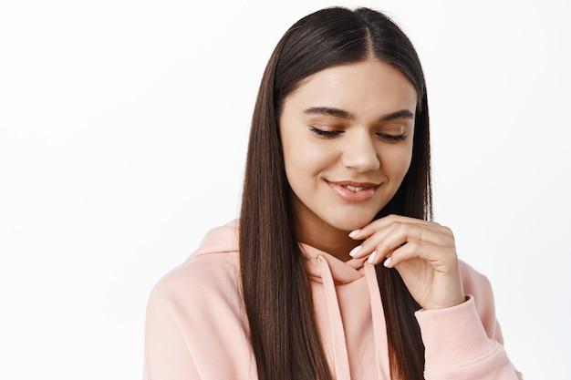 Portret van een jonge brunette vrouw die haar blik verbergt, naar beneden kijkt en sensueel glimlacht, een schoon, glad gezicht aanraakt met natuurlijke make-up, tegen een witte muur staat