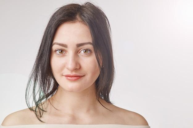 Portret van een jonge brunette vrouw gekleed in shirt met blote schouders