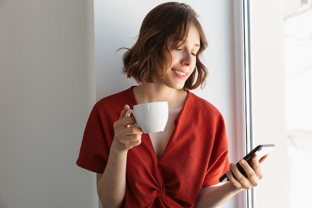 Portret van een jonge brunette vrouw gekleed in vrijetijdskleding die koffie drinkt en smartphone gebruikt terwijl ze thuis boven het raam zit