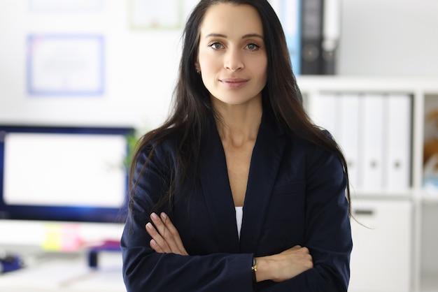 Portret van een jonge brunette vrouw in pak in kantooruitvoering van vrouwen in het bedrijfsleven