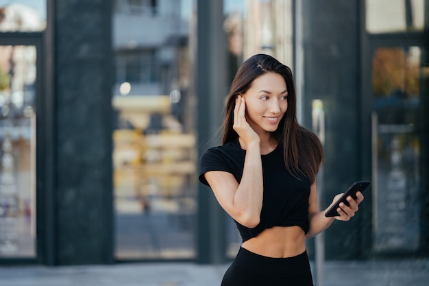 Portret van een jonge brunette vrouw met koptelefoon en lachend tijdens het wandelen