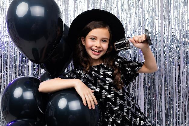 Portret van een jonge brunette zangeres in een zwarte jurk zingen met een microfoon in haar handen op een glanzend in helium ballonnen