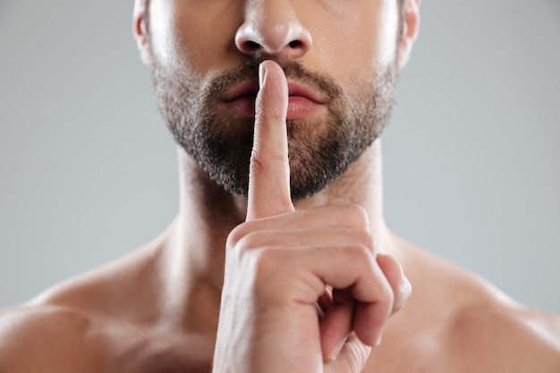 Portret van een jonge charmante naakte man met stilte gebaar
