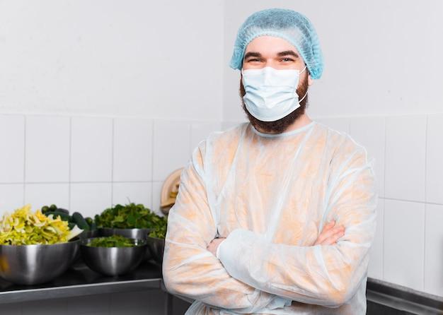 Portret van een jonge chef-kok man met gekruiste armen in de keuken