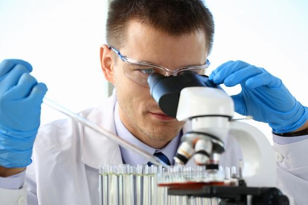 Portret van een jonge chemicus die in binoculair kijkt