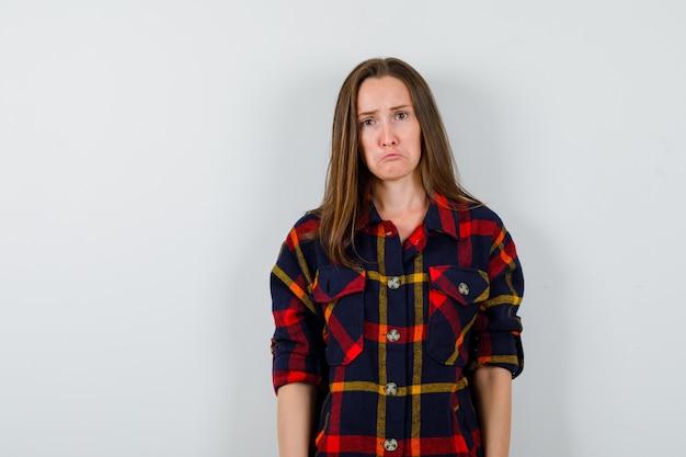 Portret van een jonge dame camera in casual shirt kijken en triest vooraanzicht kijken