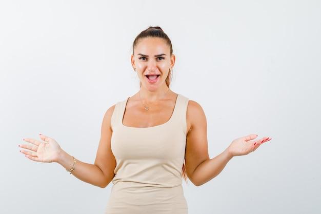 Portret van een jonge dame die de armen wijd uitgespreid houdt in beige tanktop en gelukkig vooraanzicht kijkt