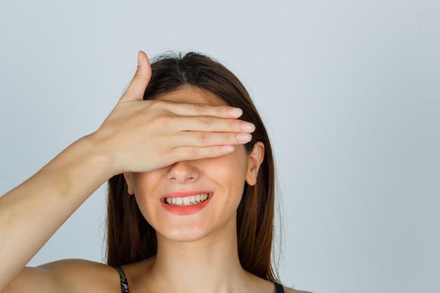 Portret van een jonge dame die de hand op de ogen in de top houdt en er vrolijk vooraanzicht uitziet