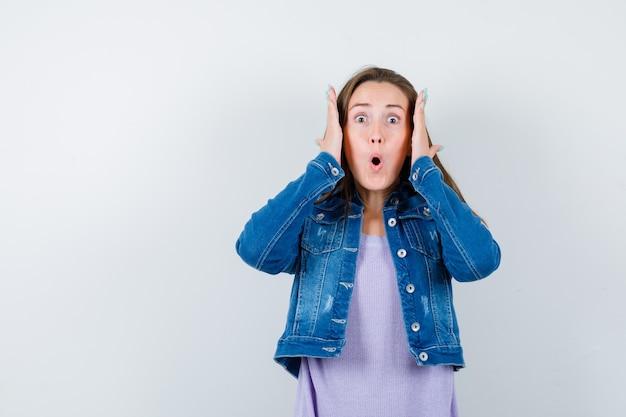 Portret van een jonge dame die de handen in de buurt van het hoofd in een t-shirt, jas houdt en een opgewonden vooraanzicht kijkt