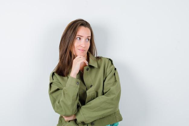 Portret van een jonge dame die de kin bij de hand houdt, wegkijkt in een groen jasje en peinzend vooraanzicht