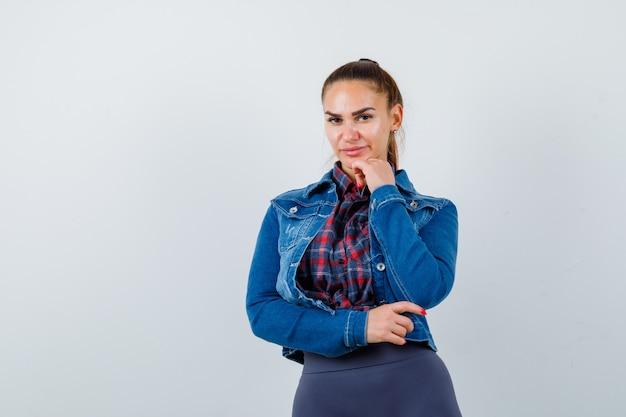 Portret van een jonge dame die de kin in haar shirt, jas steekt en peinzend vooraanzicht kijkt