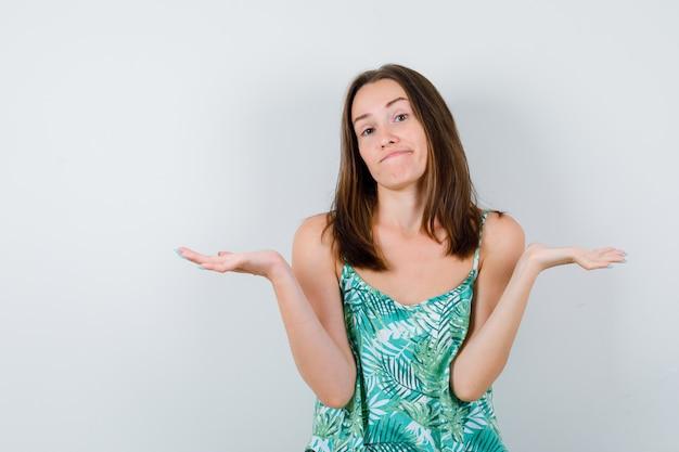 Portret van een jonge dame die doet alsof ze iets in een blouse vasthoudt en aarzelend vooraanzicht kijkt