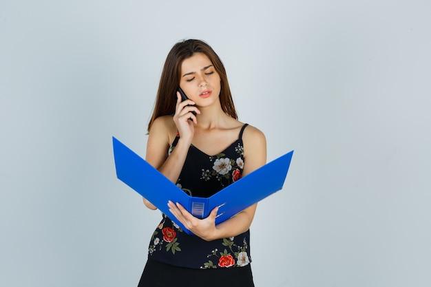 Portret van een jonge dame die door de map kijkt terwijl ze op een mobiele telefoon in een blouse praat en peinzend vooraanzicht kijkt