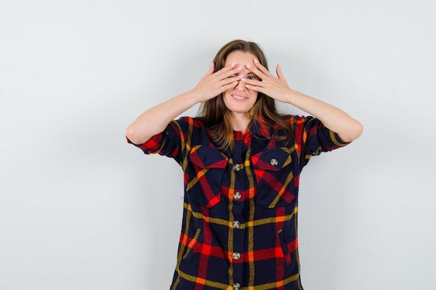Portret van een jonge dame die door vingers in casual overhemd kijkt en nieuwsgierig vooraanzicht kijkt