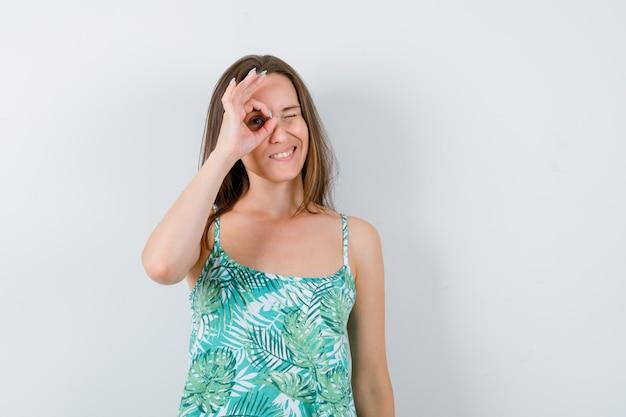 Portret van een jonge dame die een goed gebaar op het oog in een blouse toont en er zelfverzekerd vooraanzicht uitziet