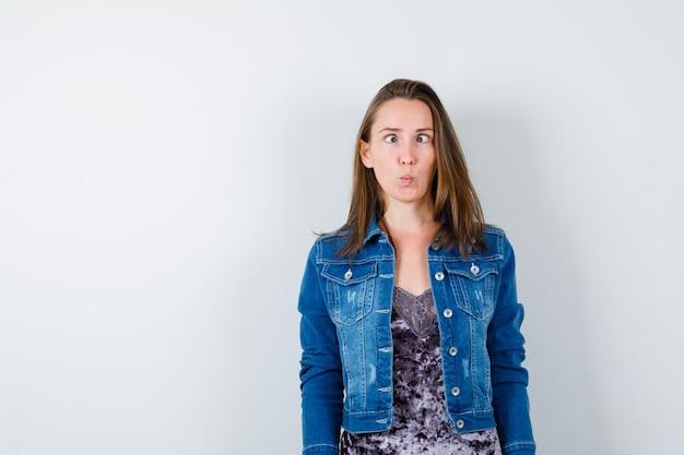 Portret van een jonge dame die een grappig vissengezicht in blouse, spijkerjasje toont en er schattig vooraanzicht uitziet