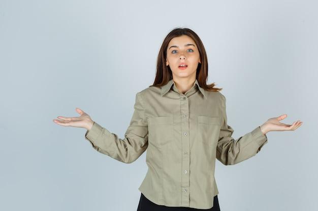 Portret van een jonge dame die een hulpeloos gebaar in shirt, rok toont en een verbaasd vooraanzicht toont