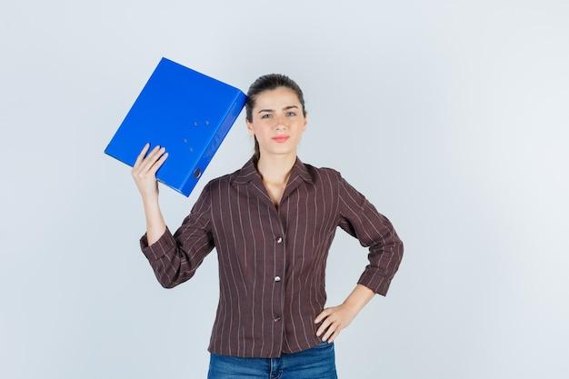 Portret van een jonge dame die een map in de buurt van het hoofd in een shirt, spijkerbroek houdt en er attent uitziet, vooraanzicht.
