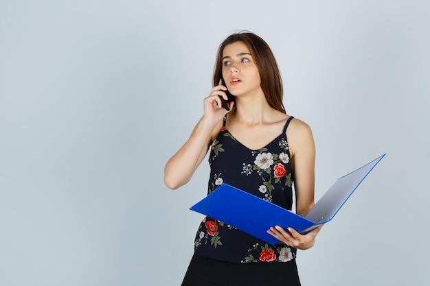 Portret van een jonge dame die een map vasthoudt, op een mobiele telefoon in een blouse praat en een peinzend vooraanzicht kijkt