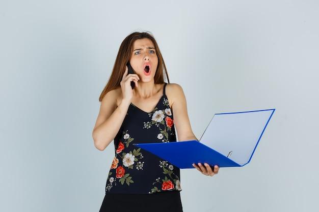 Portret van een jonge dame die een map vasthoudt, op een mobiele telefoon in een blouse praat en zich afvraagt vooraanzicht