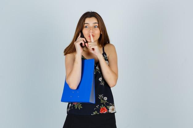Portret van een jonge dame die een map vasthoudt, op een mobiele telefoon praat, een stiltegebaar in blouse, rok toont en opgewonden vooraanzicht kijkt
