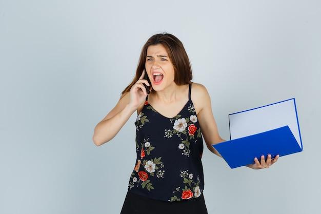 Portret van een jonge dame die een map vasthoudt, op een mobiele telefoon praat terwijl ze in een blouse schreeuwt en boos vooraanzicht kijkt