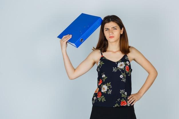 Portret van een jonge dame die een map vasthoudt terwijl ze fronst in blouse, rok en verward vooraanzicht kijkt