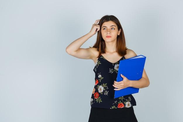 Portret van een jonge dame die een map vasthoudt terwijl ze haar hoofd krabt in blouse, rok en besluiteloos vooraanzicht kijkt