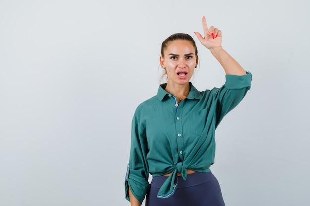 Portret van een jonge dame die een verliezer teken in een groen shirt gebaart en een geschokt vooraanzicht kijkt