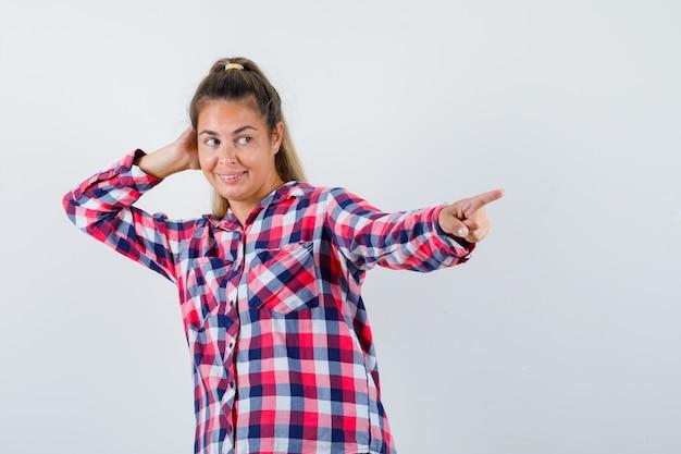 Portret van een jonge dame die ergens in een ingecheckte overhemd naar iets wijst en vreugdevol vooraanzicht kijkt