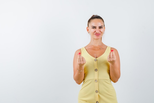 Portret van een jonge dame die geldgebaar in gele kleding maakt en vrolijk vooraanzicht kijkt