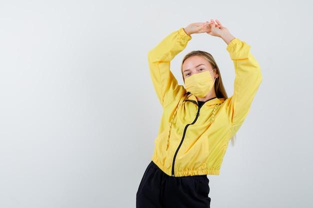 Portret van een jonge dame die gestrekte armen boven het hoofd houdt in trainingspak, masker en op zoek naar ontspannen vooraanzicht
