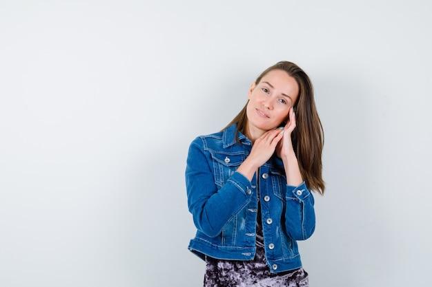Portret van een jonge dame die haar gezicht op haar handen in blouse, spijkerjasje dempt en er schattig vooraanzicht uitziet