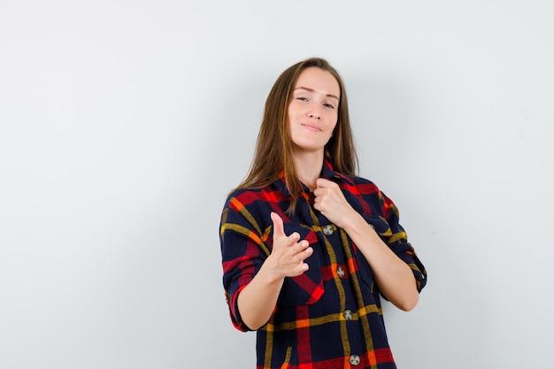 Portret van een jonge dame die hand aanbiedt om in casual overhemd te schudden en trots vooraanzicht te kijken