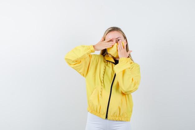 Portret van een jonge dame die hand op één oog in jas, broek, masker houdt en nieuwsgierig vooraanzicht kijkt