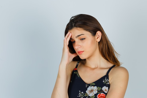 Portret van een jonge dame die hand op gezicht in bloemenbovenkant houdt en boos kijkt