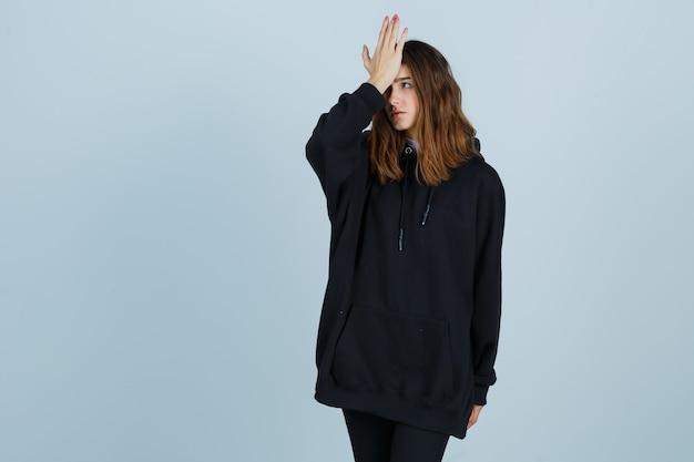 Portret van een jonge dame die hand op voorhoofd in oversized hoodie, broek en op zoek vergeetachtig vooraanzicht