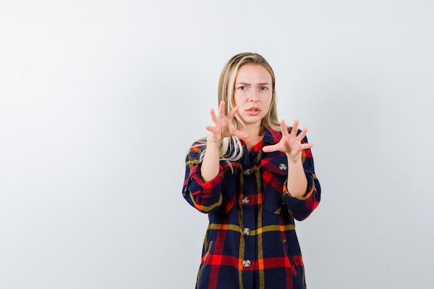 Portret van een jonge dame die handen op agressieve manier in geruit overhemd houdt en ernstig vooraanzicht kijkt
