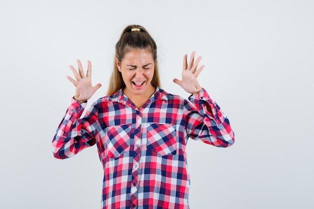 Portret van een jonge dame die handen opheft terwijl ze in geruit overhemd schreeuwt en gelukkig vooraanzicht kijkt