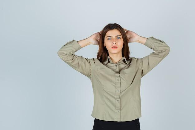 Portret van een jonge dame die handen vasthoudt achter het hoofd in hemd, rok en weemoedig vooraanzicht kijkt