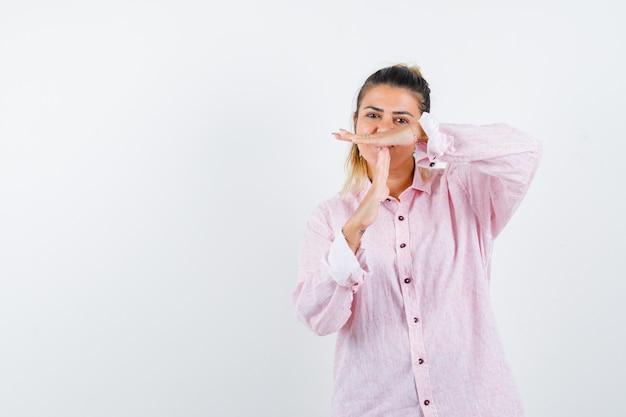 Portret van een jonge dame die het gebaar van de tijdpauze in roze overhemd toont en gelukkig vooraanzicht kijkt