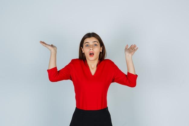 Portret van een jonge dame die hulpeloos gebaar in rode blouse toont