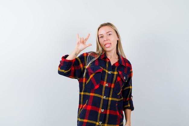 Portret van een jonge dame die i love you-gebaar in geruit overhemd toont en energiek vooraanzicht kijkt